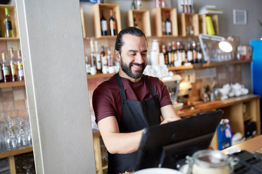 happy bartender using ordyx bar pos system at his restaurant