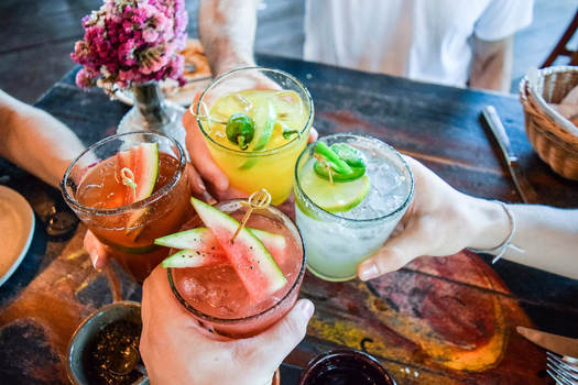4 customers cheers cocktails during happy hour